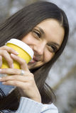 Beautiful girl in a park drinking coffee Royalty Free Stock Image