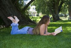 Beautiful Girl in the Park Reading a Book Royalty Free Stock Photos