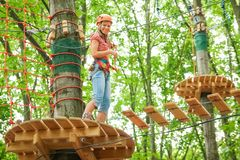 Beautiful girl in the park on the ropes achieve Outdoors stock photography