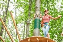 Beautiful girl in the park on the ropes achieve Outdoors royalty free stock photo