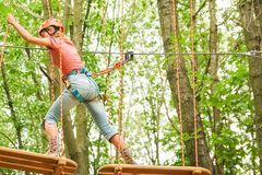 Beautiful girl in the park on the ropes achieve Outdoors royalty free stock image