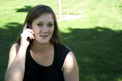 Beautiful Girl in the Park Talking on the Phone Royalty Free Stock Images