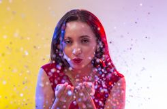 Beautiful girl on party. Background blowing confetti Royalty Free Stock Images