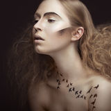 Beautiful girl with a pattern on the body in the form of birds, creative makeup and hairstyle lush. Beauty face. Stock Photography