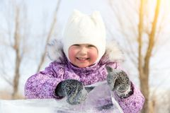 Beautiful girl peeks out from behind a pile of ice. royalty free stock image