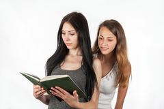 Beautiful girl peeping into girlfriend's book Royalty Free Stock Image