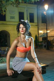 Beautiful girl with perfect body. Beautiful girl in orange bra and short skirt waits at night in park Stock Photography