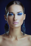 Beautiful girl with perfect skin in blue bright make-up in long earrings Stock Photos