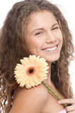 Beautiful girl with perfect skin and flower. Closeup portrait of young happy beautiful girl with perfect skin, curly hair and tender gerbera flower Stock Image