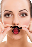 Beautiful girl with perfect skin holding fake mustache Stock Photography