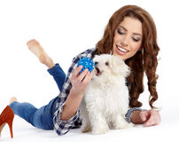 Beautiful girl with perfect skin and long wavy hair with a fluff. Y white dog on a white background Royalty Free Stock Photography