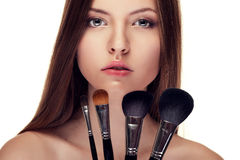 Beautiful girl with perfect skin and make up brushes Stock Photos