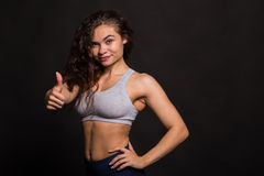 Beautiful girl performing sports exercises on a dark background Royalty Free Stock Photography