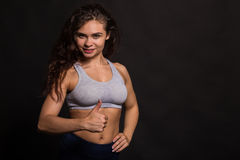 Beautiful girl performing sports exercises on a dark background Stock Image