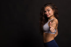Beautiful girl performing sports exercises on a dark background Royalty Free Stock Images