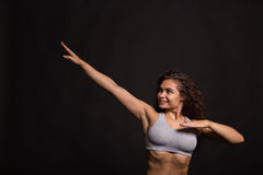 Beautiful girl performing sports exercises on a dark background Stock Photos