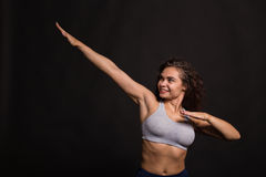 Beautiful girl performing sports exercises on a dark background Stock Photo