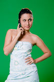 Beautiful girl on the phone. Young woman speaking on a mobile phone smiling on green background Royalty Free Stock Images