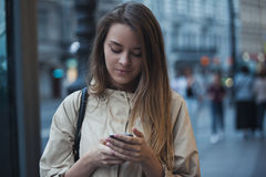 Beautiful girl with the phone in the evening city Royalty Free Stock Image