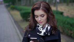 Beautiful girl with the phone on the street stock footage