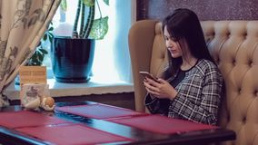 Beautiful girl with the phone. Woman using app on smartphone in cafe. Texting on mobile phone. stock footage