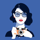 Beautiful girl photographed on a vintage camera, isolated on blue background Stock Photos