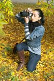 Beautiful girl photographer knee on nature Royalty Free Stock Photo