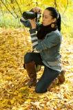 Beautiful girl photographer knee on nature (backli Stock Images