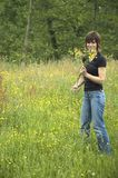 Beautiful girl picking flowers. Out of the grass fields for her boyfriend stock photos