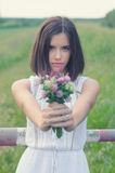 Beautiful girl picking flowers in nature on cloudy summer day Royalty Free Stock Photo