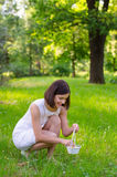 Beautiful girl picking spring flowers in small white basket Stock Images