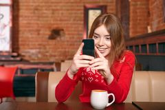 Beautiful girl picking up sms on mobile phone in cafe. Stock Photo