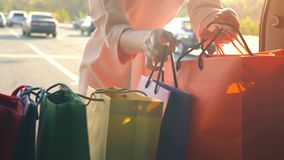 Beautiful girl picks up shopping bags from the trunk of the car, closes it and leaves. Shopping concept stock video