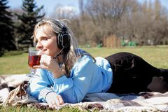 Beautiful girl on picnic listening to music in headphones and with a cup in hand Stock Image