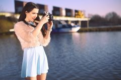 Beautiful girl on the pier near the river. Model in blue dress with long hair. Girl at hot sunny day taking pictures on old camera stock images