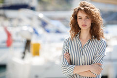 Beautiful girl on the pier next to the yacht club Stock Photo