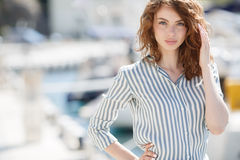 Beautiful girl on the pier next to the yacht club Royalty Free Stock Image