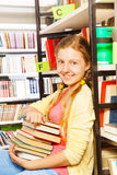 Beautiful girl with pile of books sit near shelf Royalty Free Stock Photo