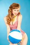Beautiful girl pin-up in a pink bikini with beach ball royalty free stock photography