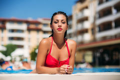 A beautiful girl in a pink bathing suit sunbathing by the pool. Sunny weather.