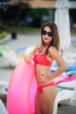 A beautiful girl in a pink bathing suit sunbathing by the swimming pool .Sunny weather. Summer. Royalty Free Stock Photos
