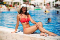 A beautiful girl in a pink bathing suit sunbathing by the swimming pool .Sunny weather. Summer. Stock Image