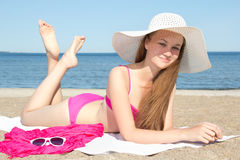 Beautiful girl in pink bikini and white hat lying on the beach Royalty Free Stock Photos