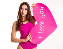 Beautiful girl in pink bodi holding paper heart. Pretty slim teenager girl is wearing pink sexy bodi holding big paper hearts isolated on white background Stock Images