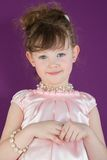 Beautiful girl in a pink dress. With a beads and a bracelet of pearls stock images