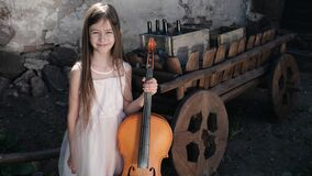 Beautiful girl in a pink dress with a cello in the village
