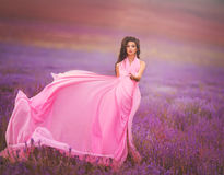 Beautiful girl in a pink dress flying in a lavender field stock photo