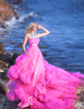 Beautiful girl in a pink dress on the ocean in a pink dress stock photography