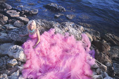 Beautiful girl in a pink dress on the ocean in a pink dress stock photo
