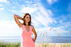 Girl in pink dress on seacoast Royalty Free Stock Images